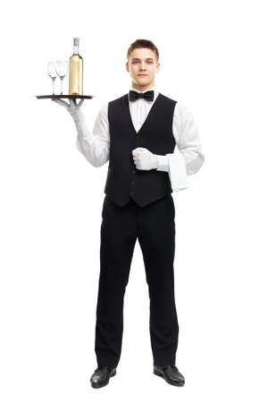 full length portrait of young happy smiling waiter with bottle of white wine and stemware glass on tray isolated on white background photo