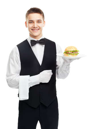 Portrait of young happy smiling waiter holding hamburger on plate isolated on white background photo