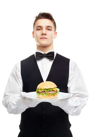 Portrait of young serious waiter holding burger on plate isolated on white background photo