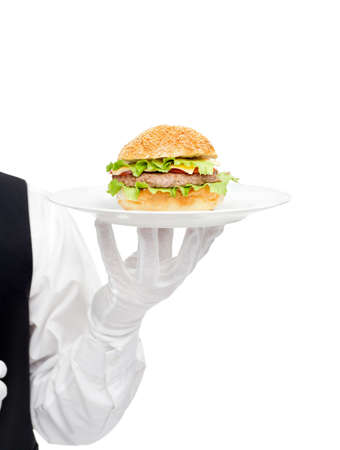Waiter hand in white gloves holding hamburger on plate isolated on white background photo
