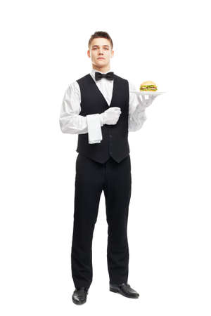 Full length portrait of young serious waiter holding hamburger on plate isolated on white background photo