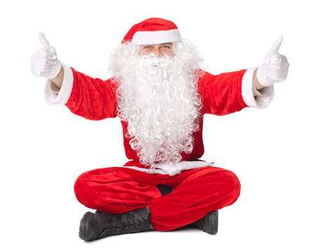 Santa Claus sitting on floor with thumb up sign isolated on white background  photo