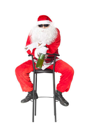 Santa Claus sitting in a chair wearing sunglasses holds a bottle of champagne and smoking a cigar isolated on white background