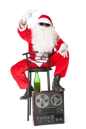 Santa Claus showing the middle finger sitting in a chair with retro audio tape recorder isolated on white background photo