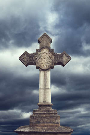 stone cross on dark sky photo