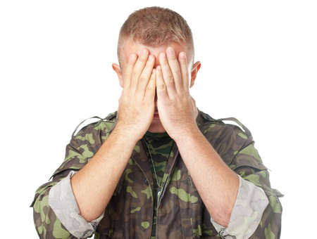 eyes closing: Closeup portrait of army soldier closing eyes with hands isolated on white background