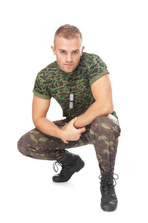 Portrait of young army soldier squatting isolated on white background photo