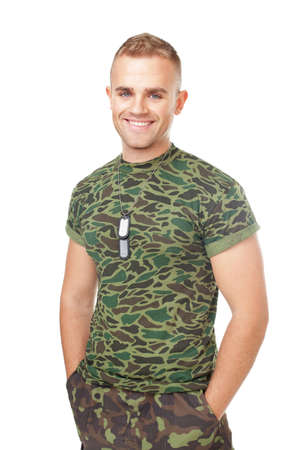 only man: Portrait of young smiling army soldier with military ID tags standing with hands in pockets isolated on white background