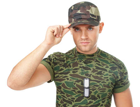 Portrait of young army soldier with military ID tags touching his cap isolated on white background photo
