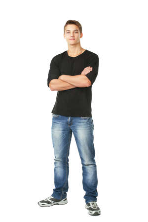 standing against: Full length portrait of young man standing with hands folded against isolated on white background