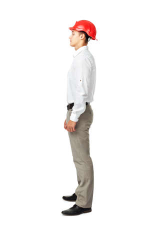 Full length side view portrait of young engineer wearing a red helmet isolated on white background photo