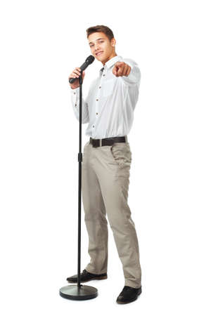 Young man singing into a microphone while pointing forward isolated on white background photo