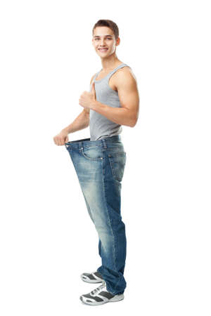 A handsome young man showing how much weight he lost whist thumb up isolated on white  Stock Photo