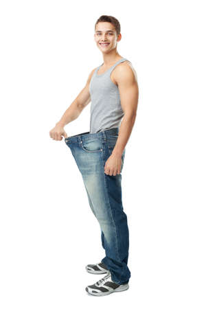 A handsome young man showing how much weight he lost isolated on white background