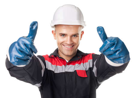 protective helmets: Portrait of young smiling worker in protective gloves giving thumb up isolated on white background