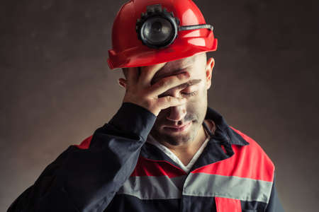 Portrait of tired coal miner holding hand his head against a dark background