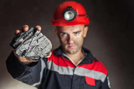 lump: Coal miner showing lump of coal against a dark background