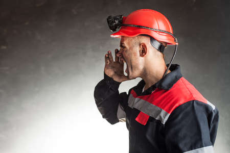 unkind: Side view portrait of angry coal miner shouting against a dark background