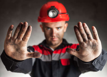Coal miner with dirty hands making stop gesture warning of danger against a dark background photo