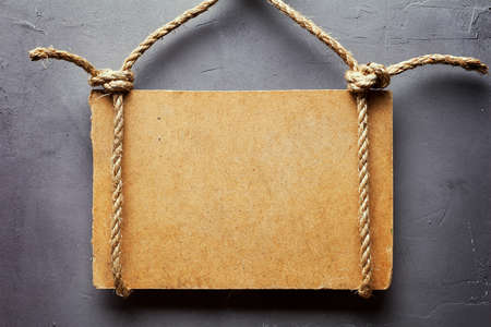 label frame: Wooden signboard with rope hanging on gray textured wall Stock Photo