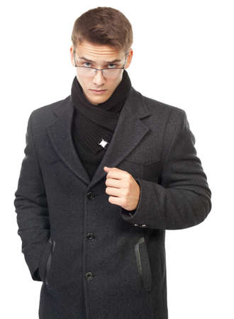 Portrait of frowning young man wearing coat looking over glasses isolated on white background photo