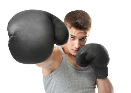 Portrait of young boxer throwing a punch at the camera isolated on white background photo