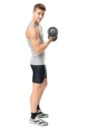 Full length portrait of young fit muscular man exercising with dumbbells for training his biceps isolated on white background