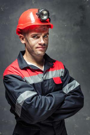 Retrato de minero de carbón serio con los brazos cruzados sobre un fondo oscuro
