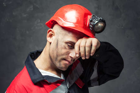 Portrait of tired coal miner wiping forehead his hand against a dark background
