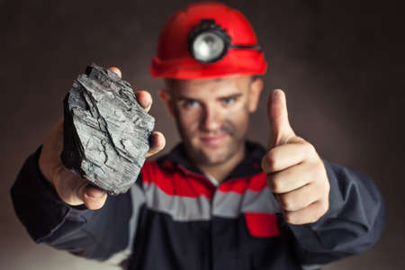 Coal miner showing lump of coal with thumbs up against a dark background photo