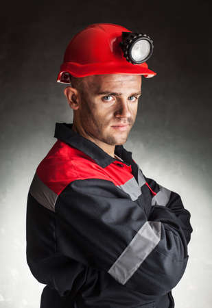 Portrait of serious coal miner with his arms crossed against a dark background photo