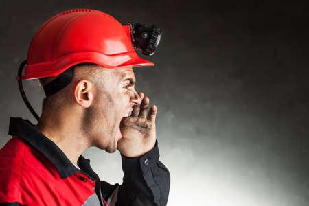 Vista lateral del retrato de enojado gritando minero de carbón contra un fondo oscuro