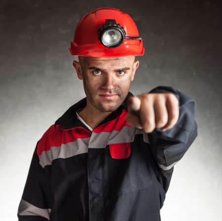Portrait of serious coal miner pointing forward against a dark background
