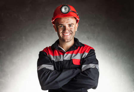 COAL MINER: Portrait of happy smiling coal miner with his arms crossed against a dark background Stock Photo