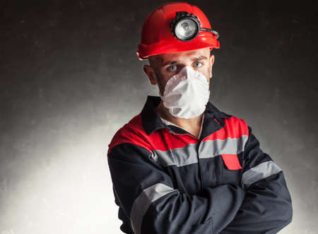 safety at work: Portrait of coal miner with white respirator on his face against a dark background