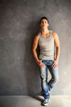 Portrait of young stylish man wearing undershirt and jeans leaning to gray textured wall photo