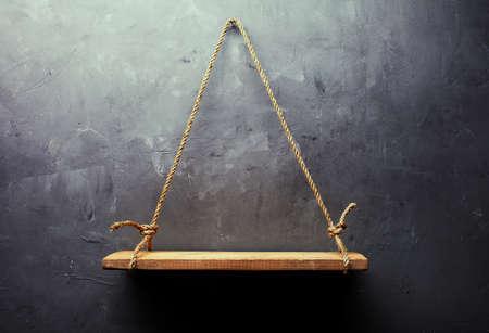 estanterias: Vacío vieja madera estante colgante de la cuerda sobre la pared de fondo con textura