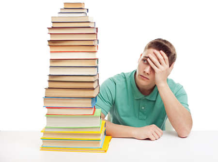 frustrated student: Young frustrated student sitting at the desk with high books stack isolated on white background  Stock Photo