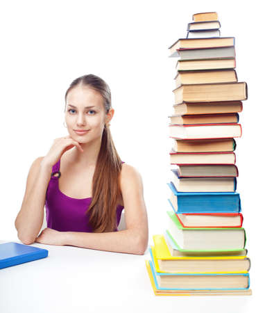 Portrait of pretty young smiling student girl sitting at the table with high stack of books isolated on white background photo