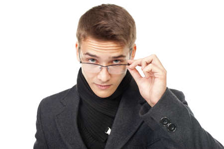 Portrait of elegant young man wearing coat looking over glasses isolated on white background photo