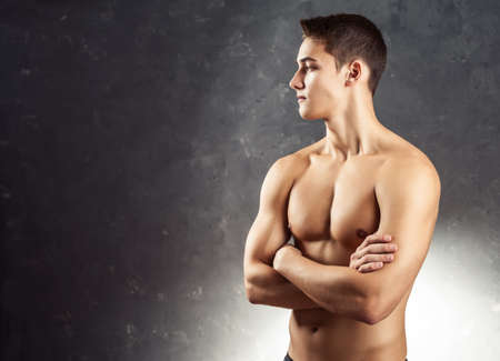 Portrait of muscular young man looking away with naked torso against gray textured background photo