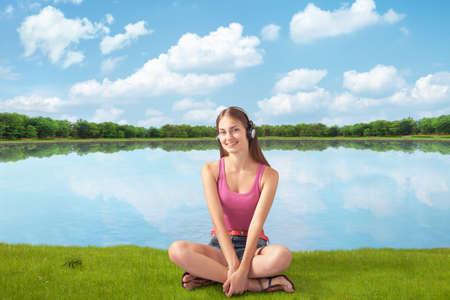 beautiful girl in headphones listens to music near river, sitting ashore  photo