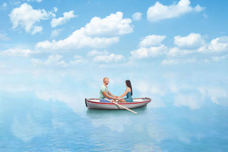 young couple in Love hold hands on boat in sea photo