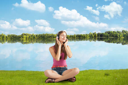 ashore: beautiful girl in headphones listens to music near river, sitting ashore  Stock Photo