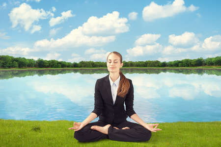 young business woman meditating sitting in Lotus Pose on grass on bank of lake