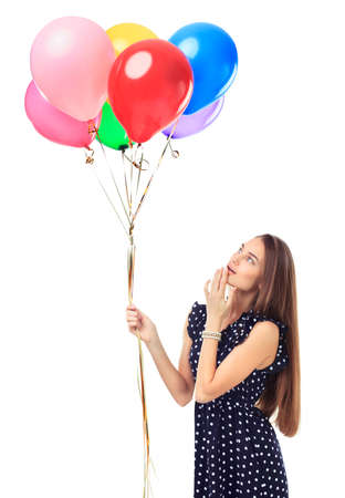 Beautiful young happy woman admiring colorful balloons in polka dot dress isolated on white background photo