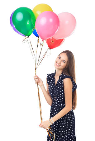 Portrait of beautiful young happy woman in polka dot dress with colorful balloons having fun isolated on white background photo
