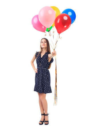 Full length portrait of beautiful young woman in polka dot dress offering colorful balloons isolated on white background photo