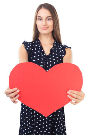 Portrait of beautiful young happy woman in polka dot dress holding red heart isolated on white background. Valentines day. photo
