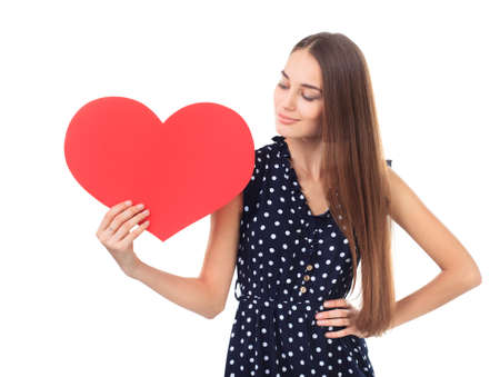 Portrait of beautiful young happy woman in polka dot dress looking at a red heart in her hand isolated on white background. Valentines day. photo